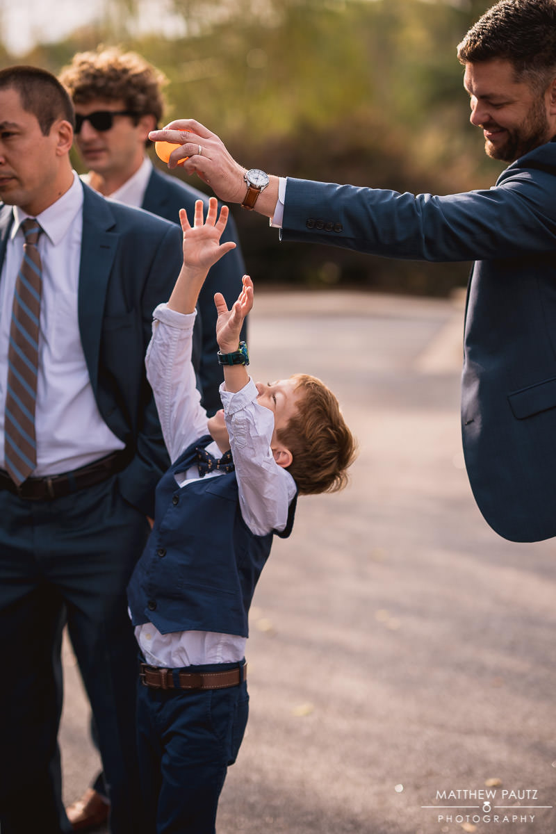 Groomsmen playing around with ring bearer before wedding