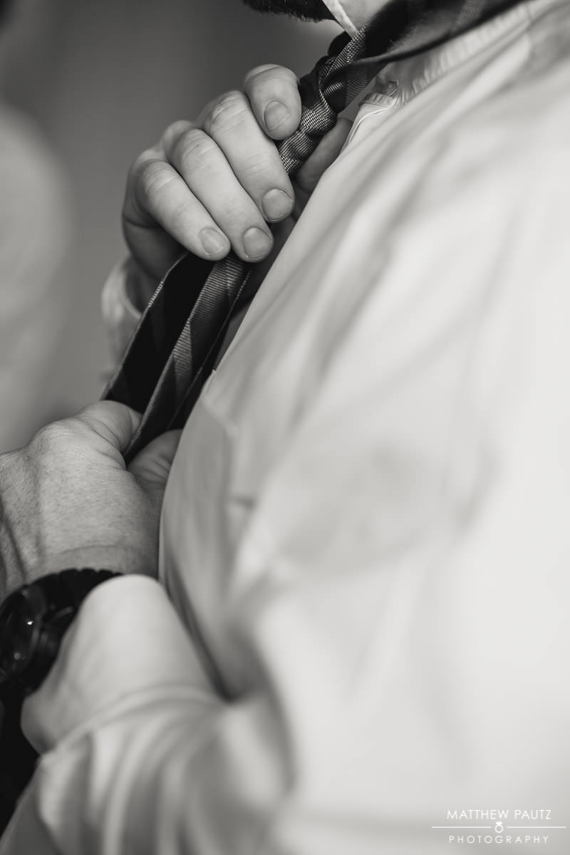 Groom adjusting tie before wedding