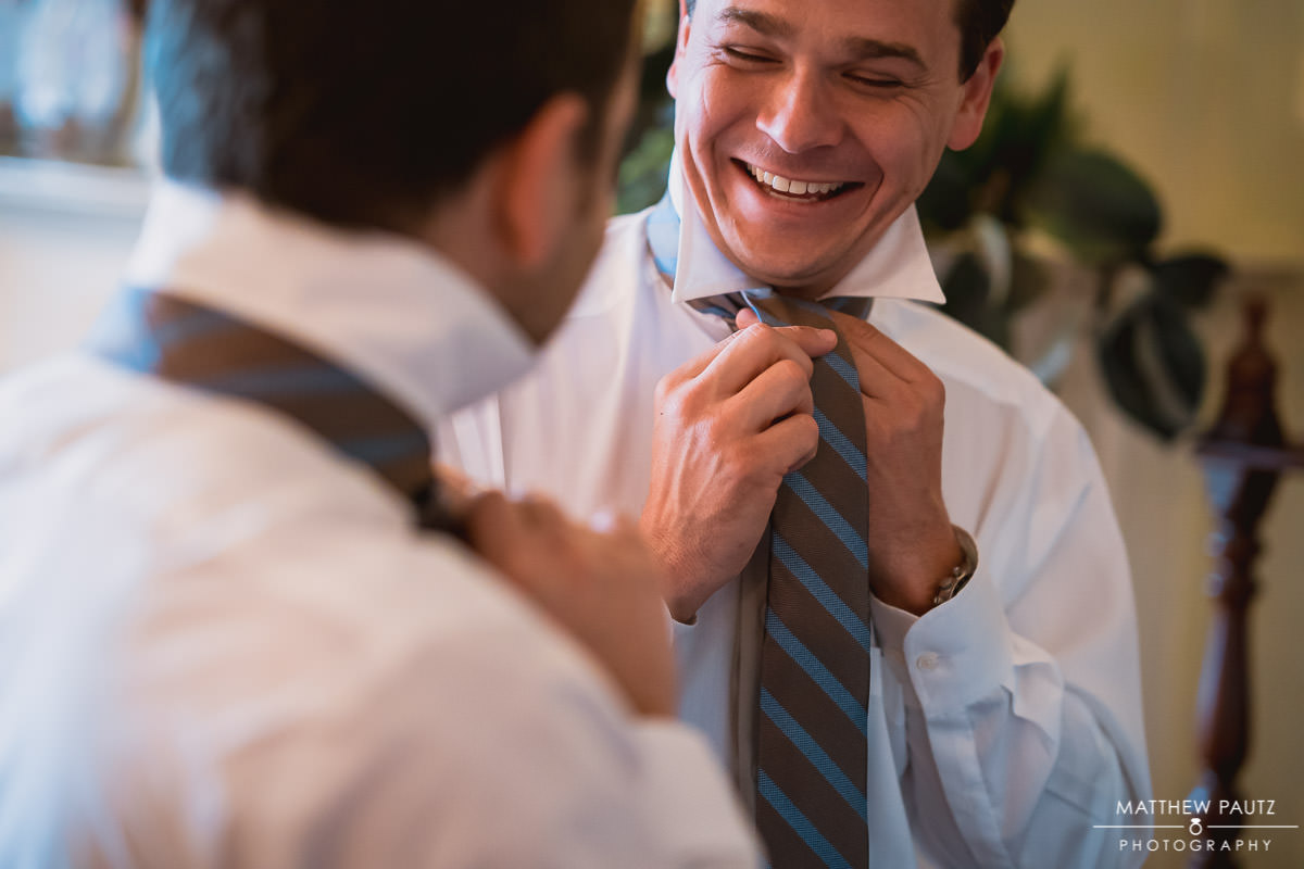 groomsmen laughing and having fun while getting ready for a wedding