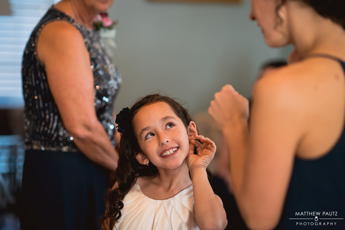 flower girl showing off ring to bridesmaid