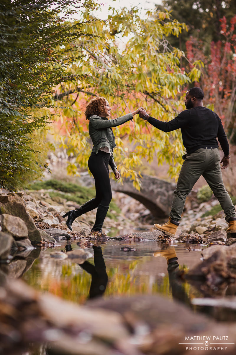Engaged couple hopping over a creek together