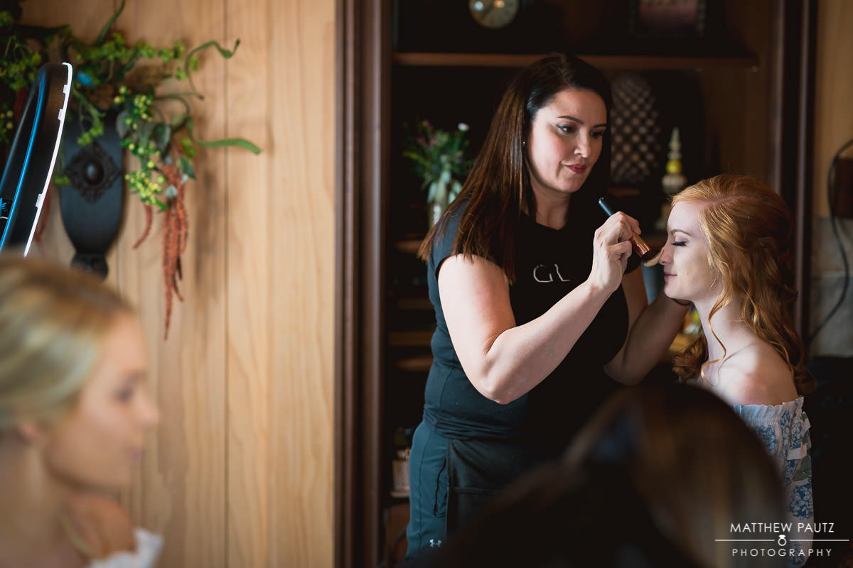 bridesmaid having makeup done while getting ready for wedding