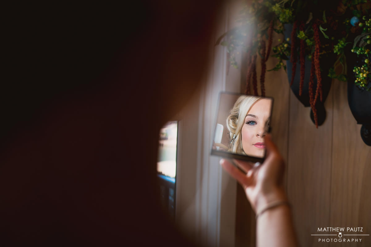 bride looking at herself through handheld mirror