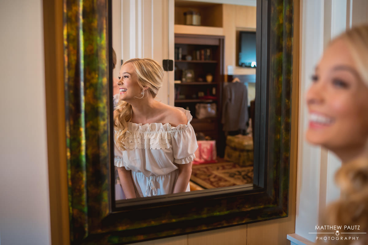 bride laughing while looking at reflection in mirror