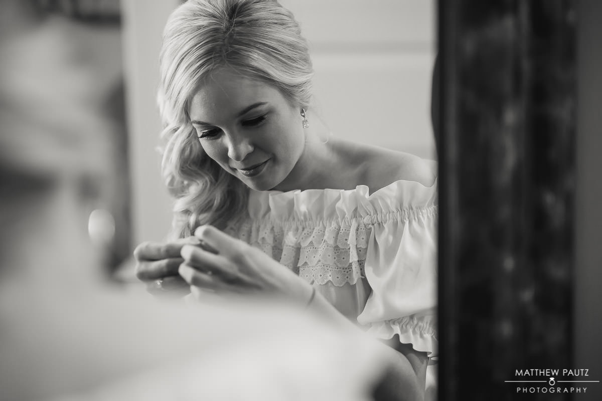 Bride putting on jewelry before wedding