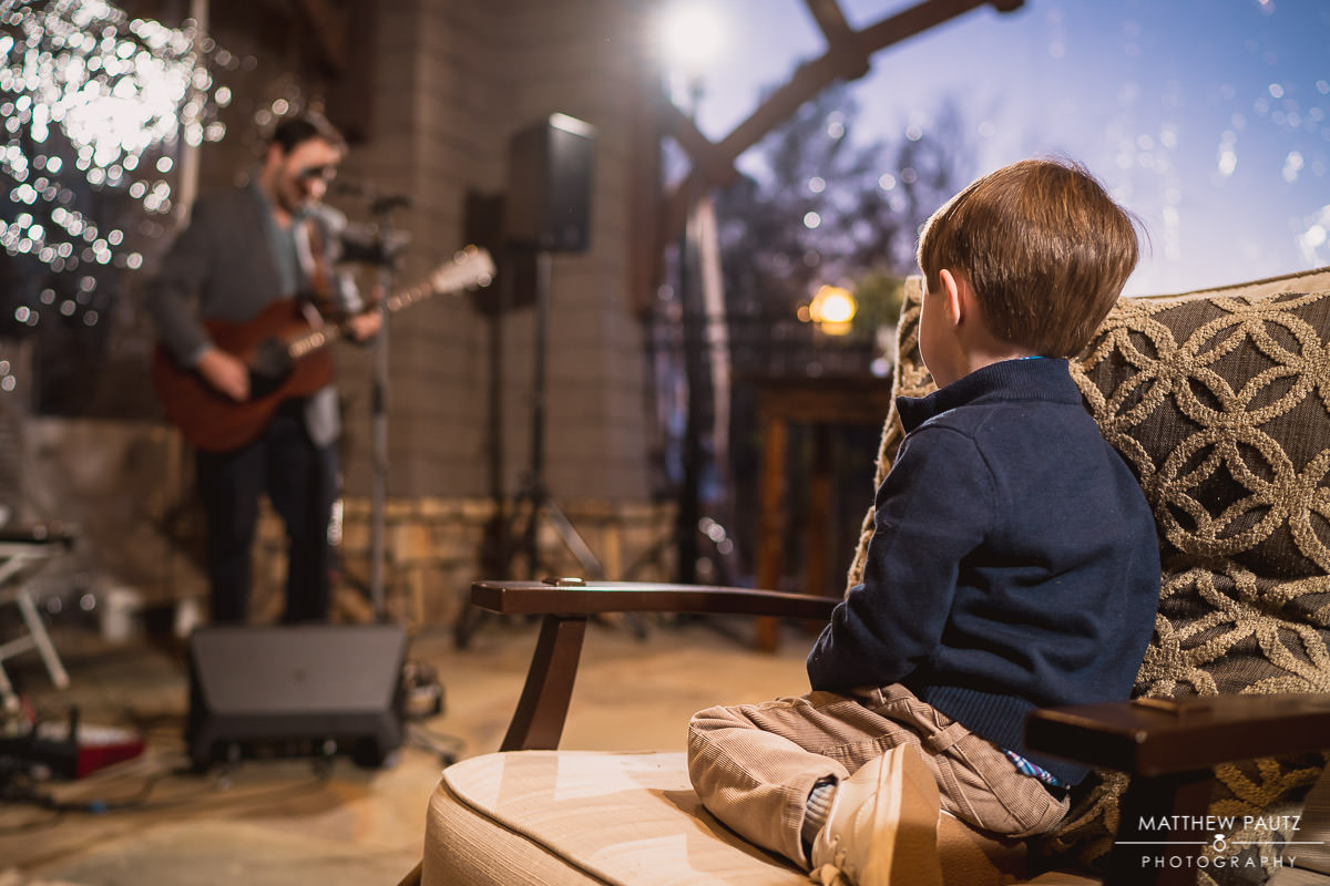 child watching guitarist perform at wedding reception