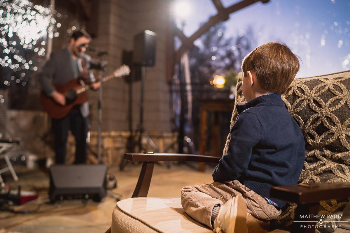 child watching guitarist perform at wedding reception