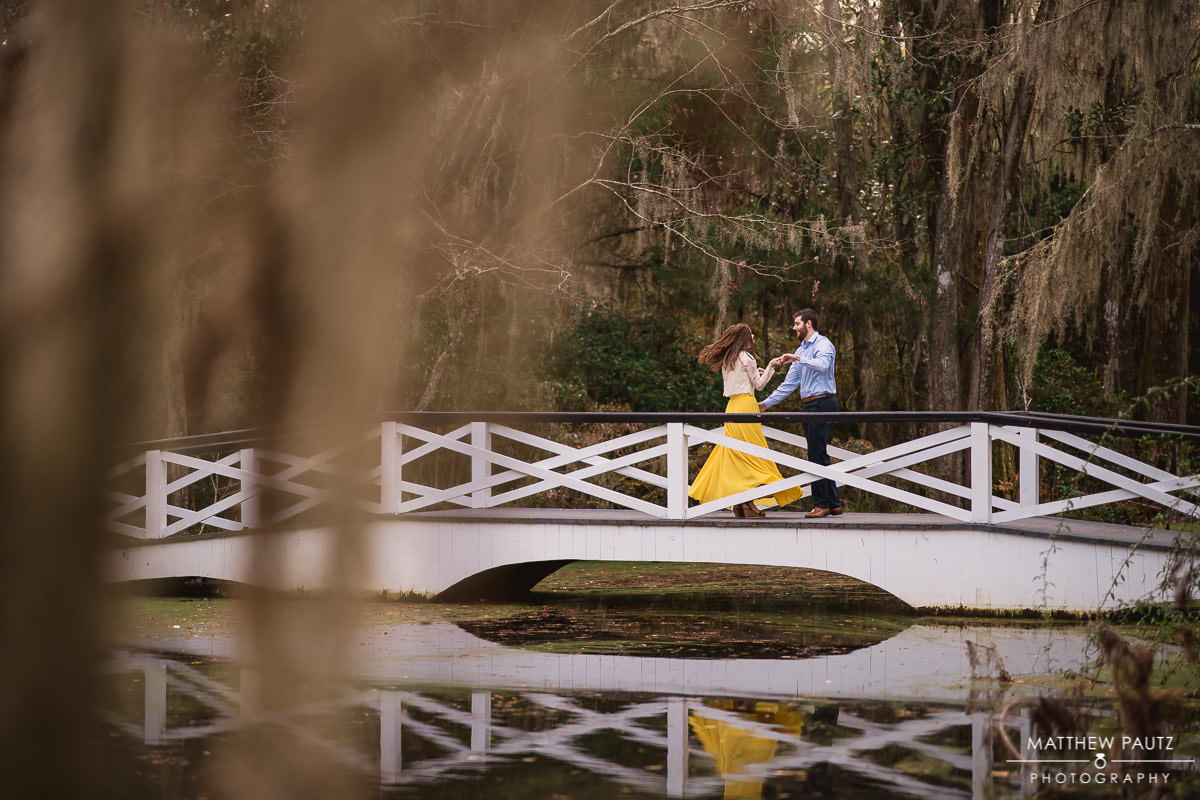 engaged couple dancing on a bridge over water in Charleston SC