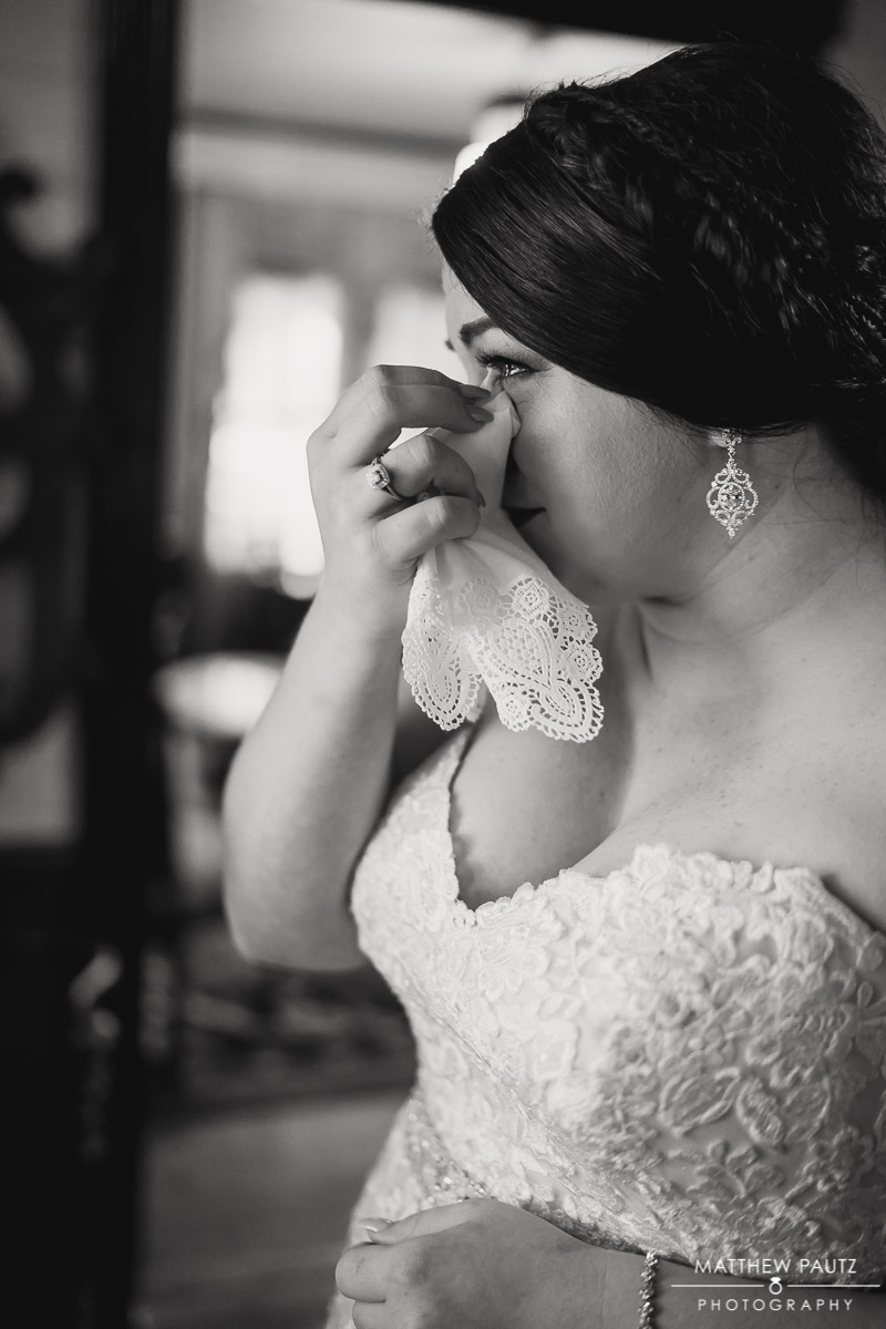 Bride drying her eyes with handkerchief while getting ready