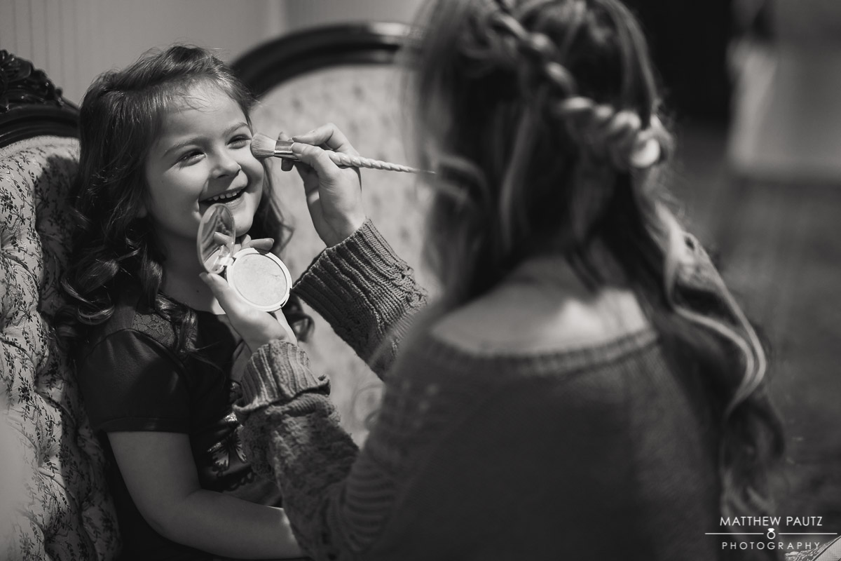 flower girl having makeup applied before wedding ceremony
