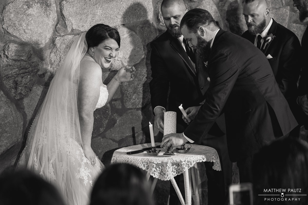 bride and groom having trouble lighting a unity candle at wedding ceremony