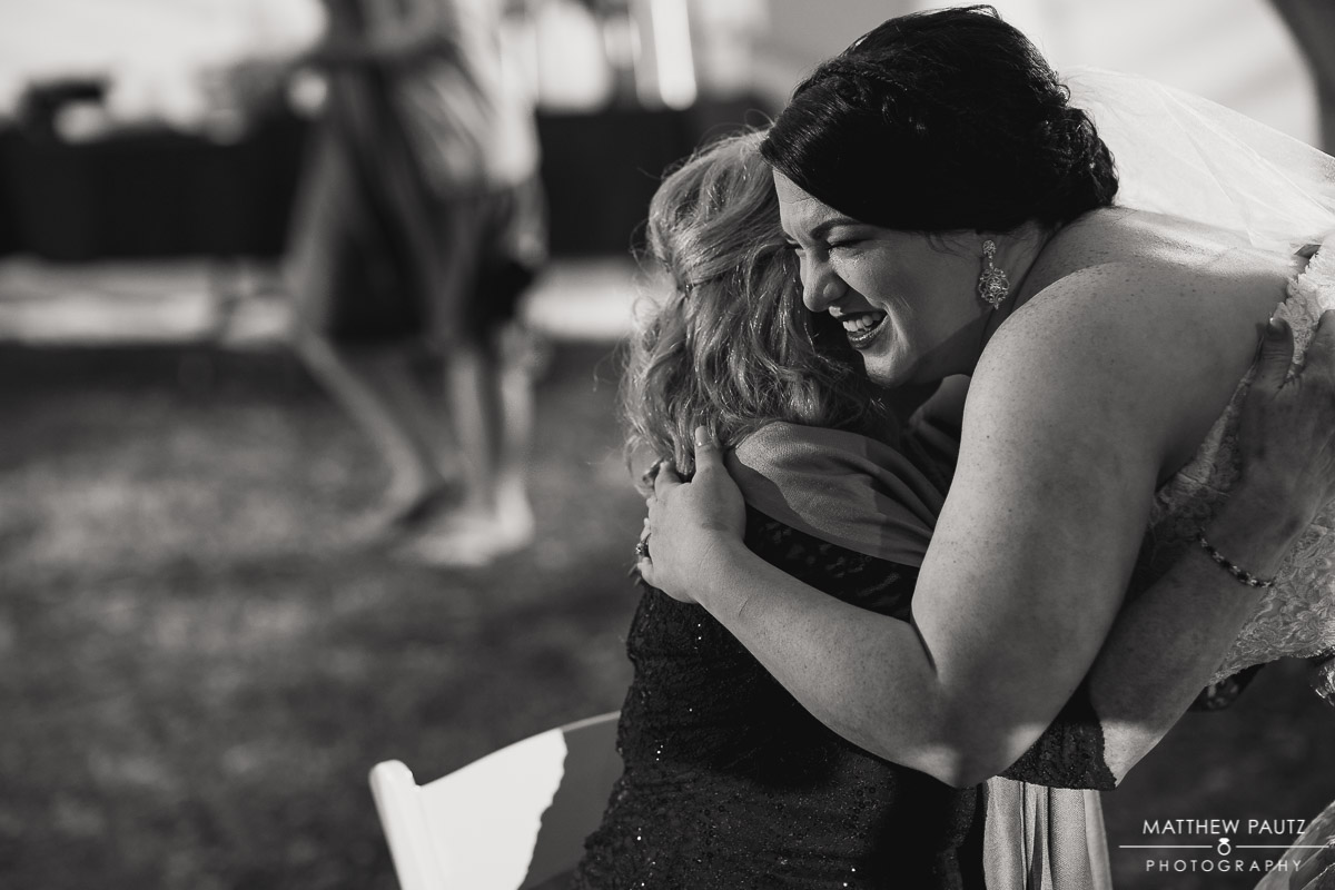 bride hugging her mother at wedding reception