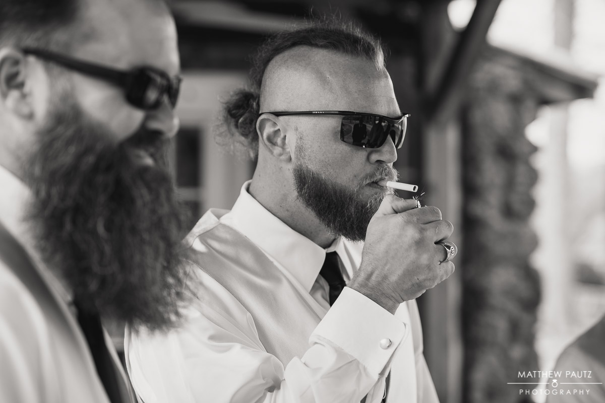 Groomsman lighting a cigarette while getting ready