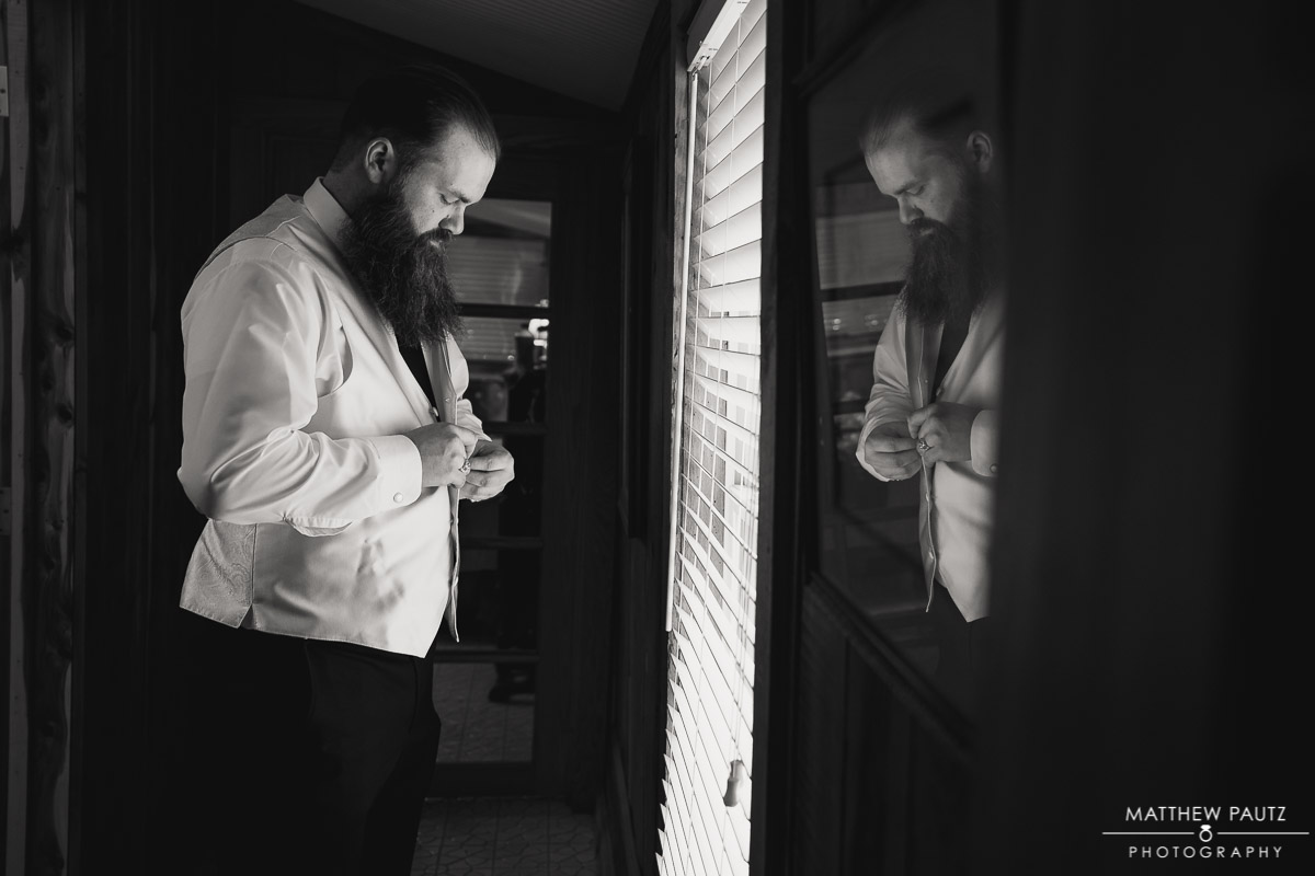 Groom buttoning up shirt before wedding