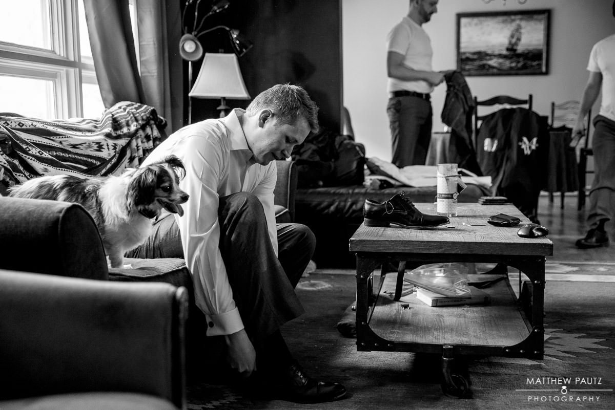 groom putting on shoes before wedding