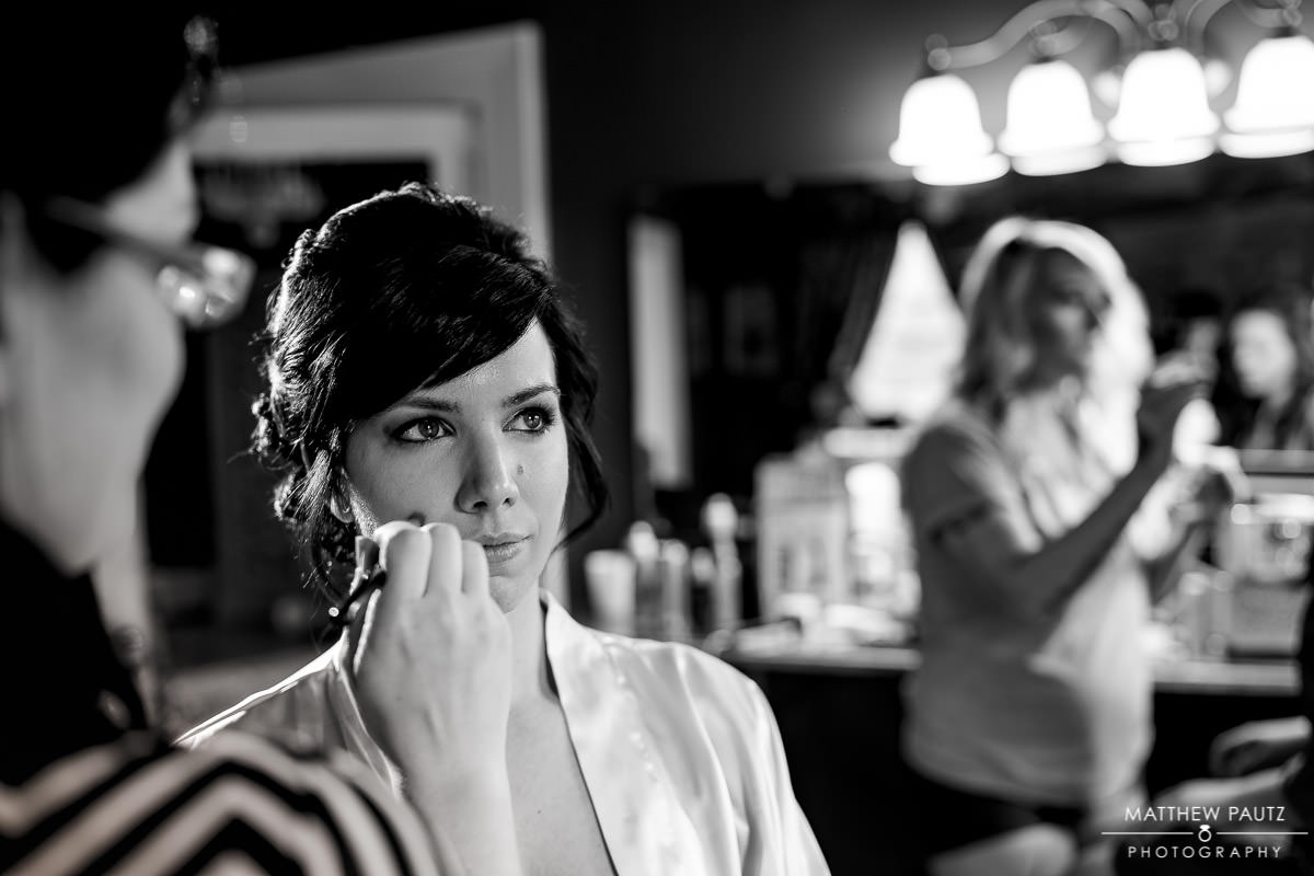 Bride having makeup done before wedding