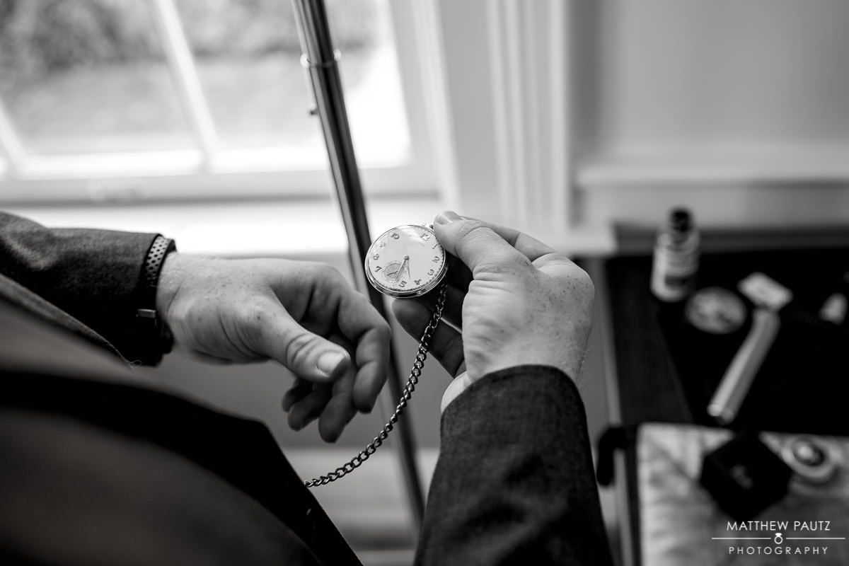 groom checking and setting pocket watch before wedding ceremony