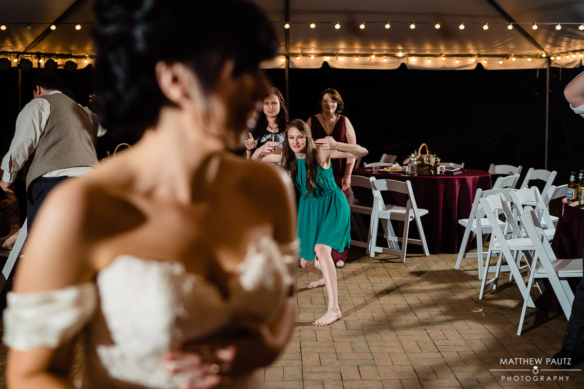 bridesmaid trying to catch the bouquet at wedding reception