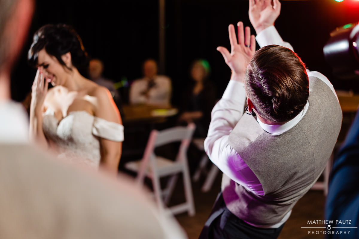 groom embarassing bride with dancing at wedding reception