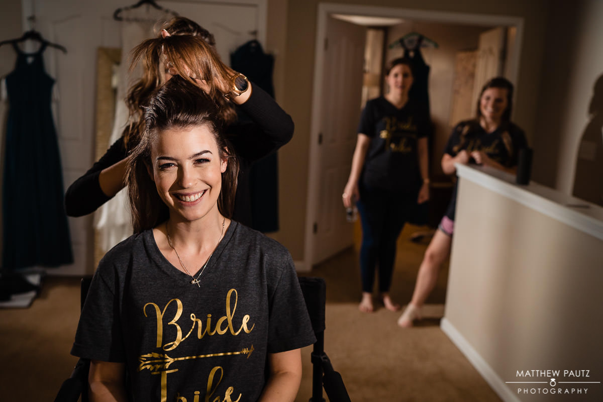 Bride preparing for wedding day with bridesmaids in background