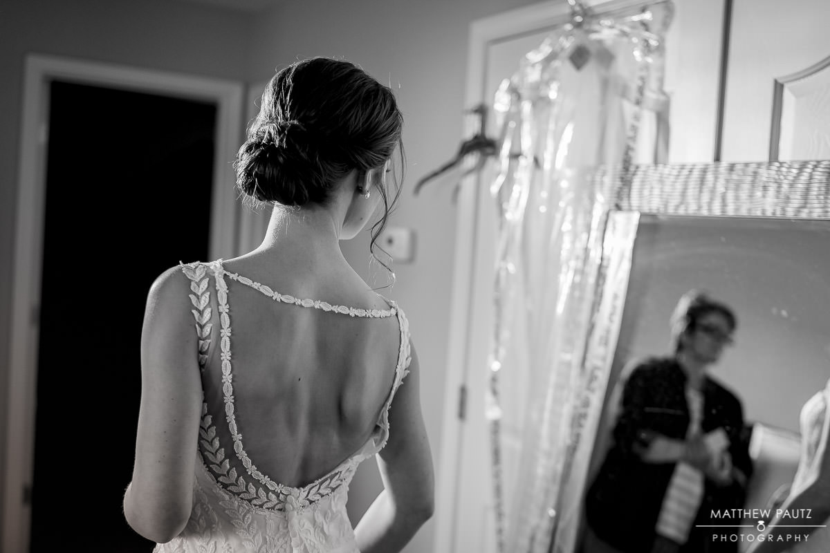 bride checking herself in mirror after getting dressed before wedding