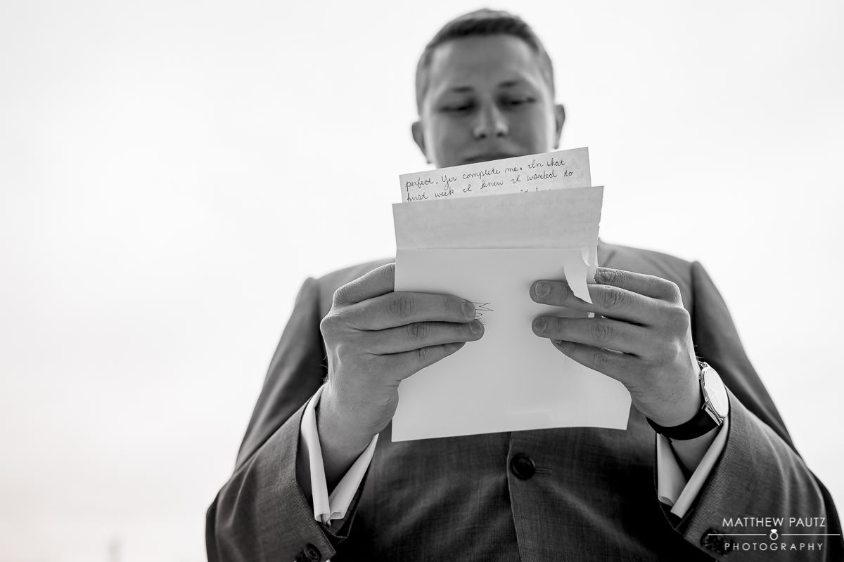 groom reading bride's letter before wedding