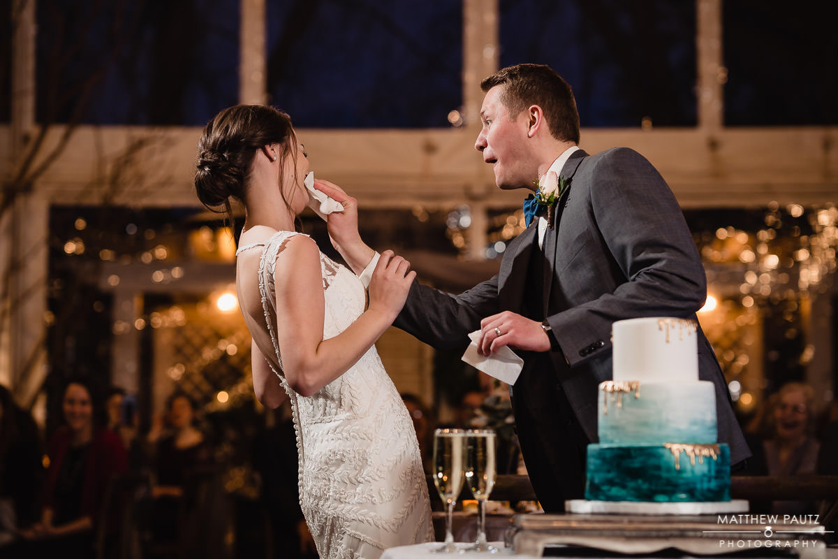groom wiping cake off bride's face