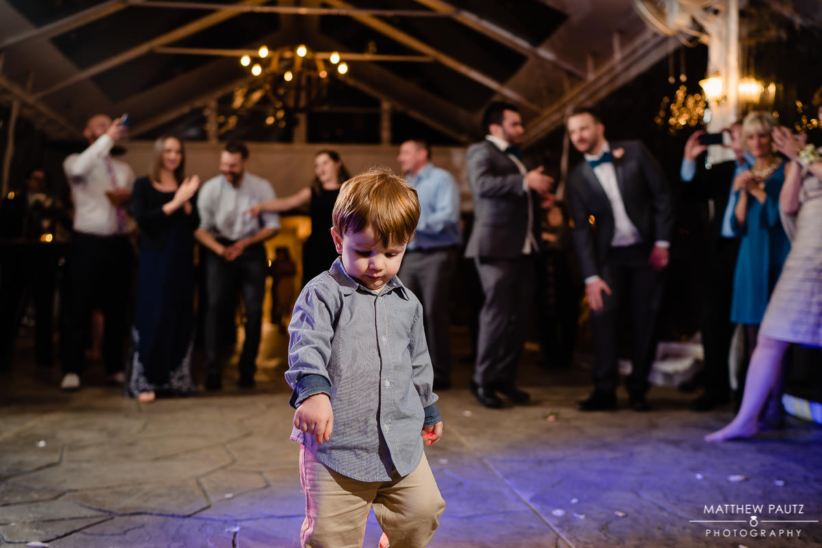 child dancing in middle of dance floor at wedding reception