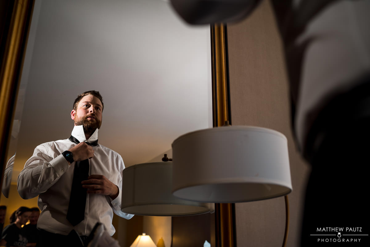groom adjusting his tie in a hotel room