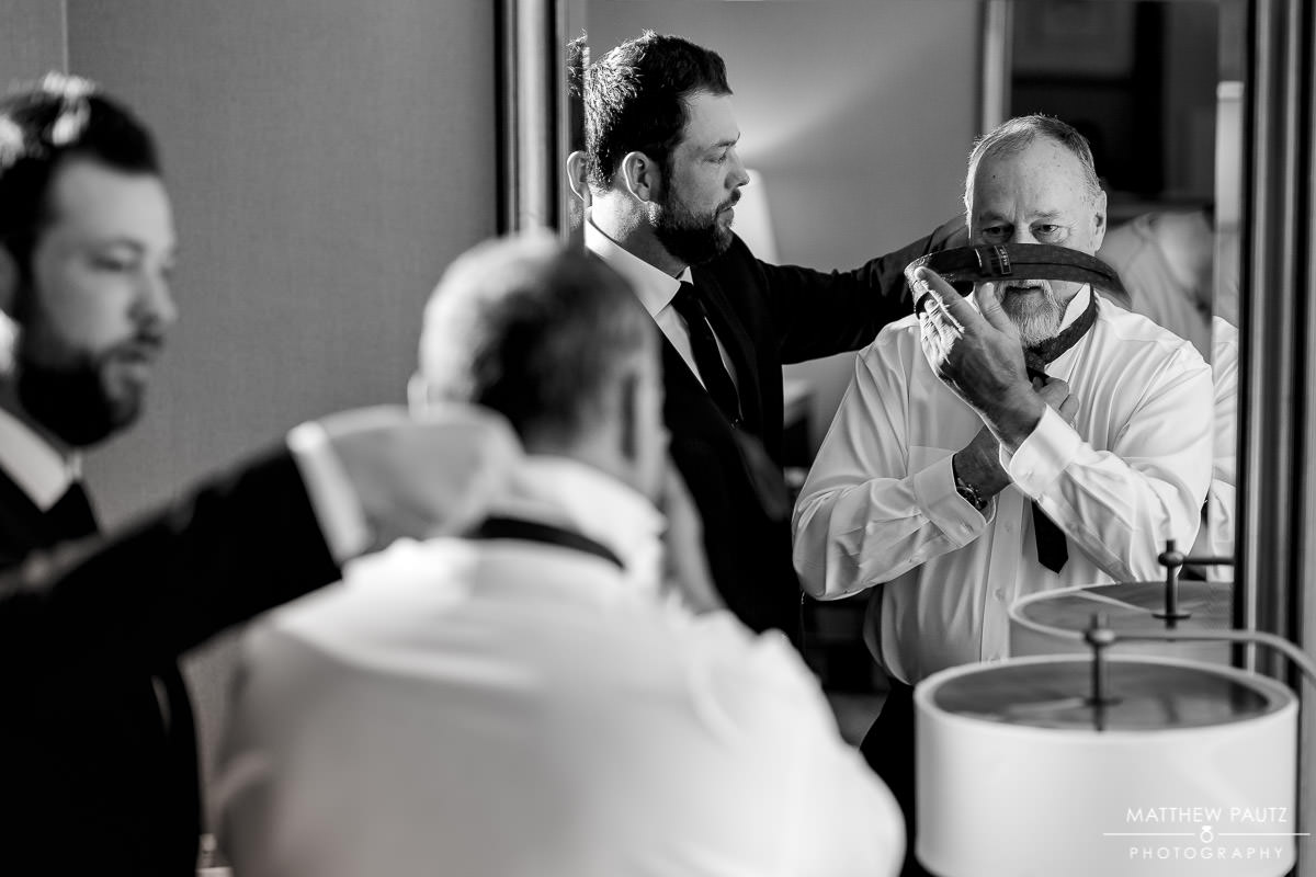 Groom helping his father tie a tie before wedding