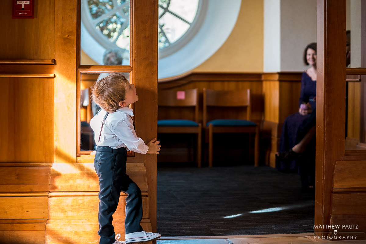 ring bearer playing around in chapel before wedding ceremony