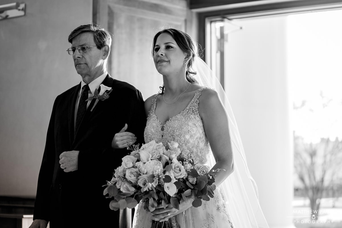 bride walking into the chapel with her father for wedding ceremony