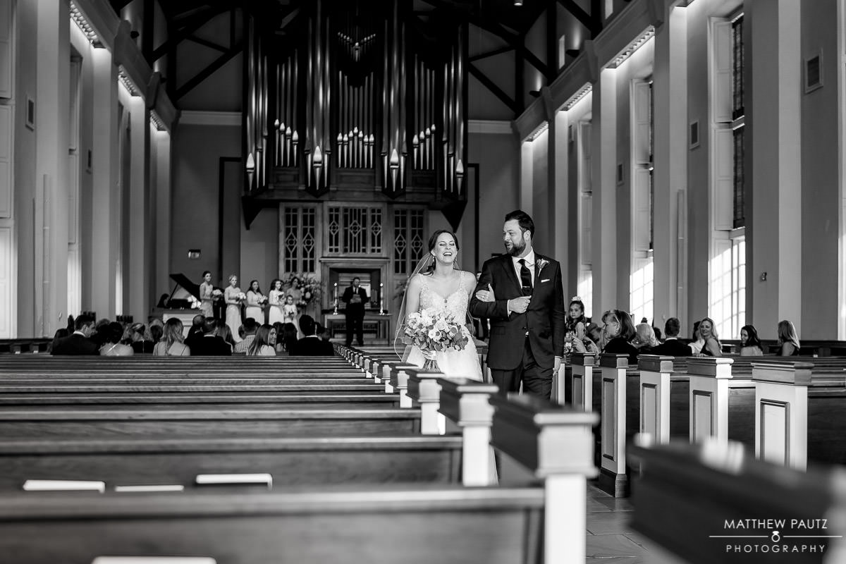 bride and groom walking down aisle together after ceremony