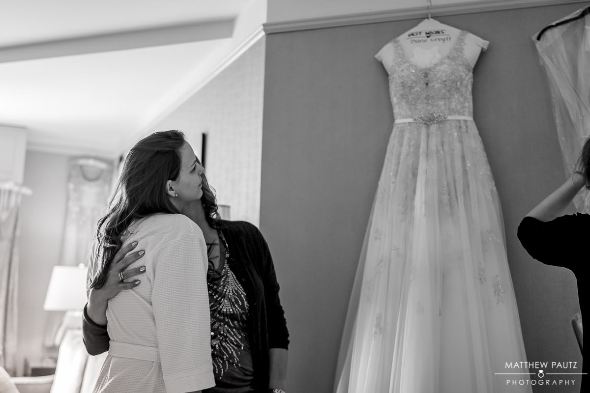 Bride looking up at her wedding dress hanging in hotel room