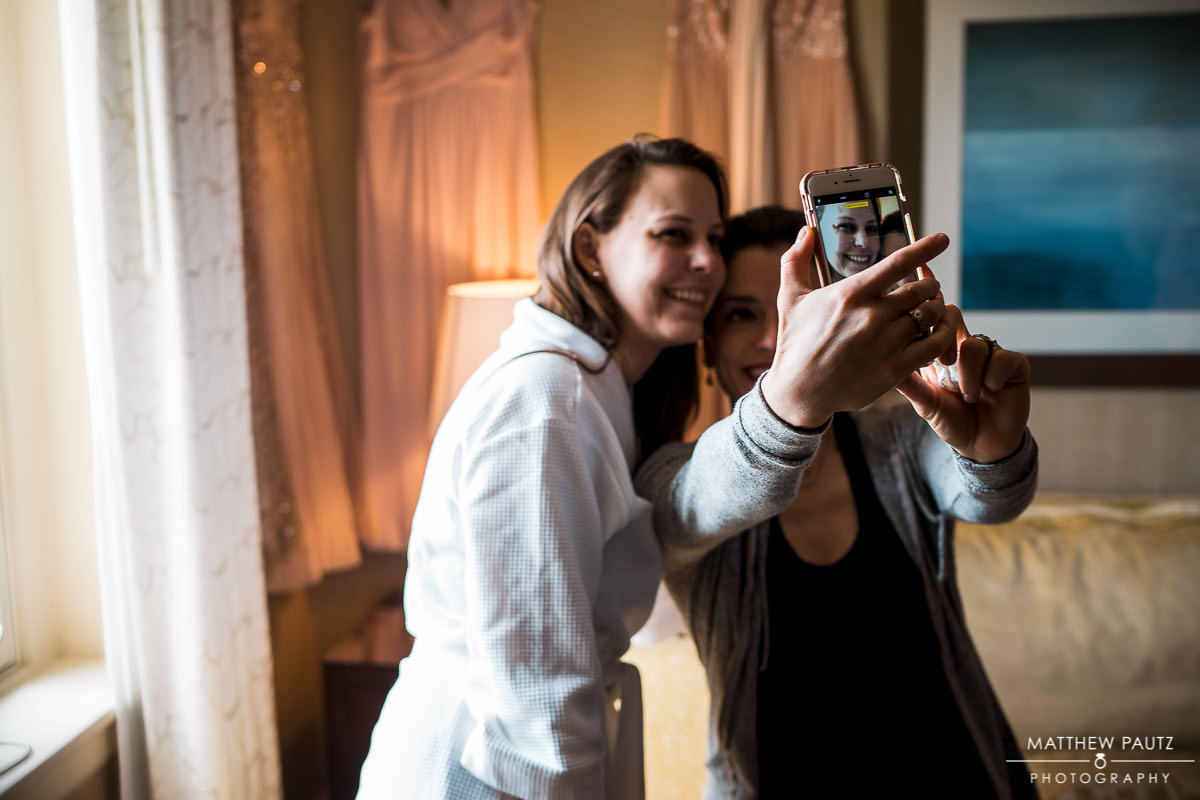 maid of honor taking selfie with bride before wedding