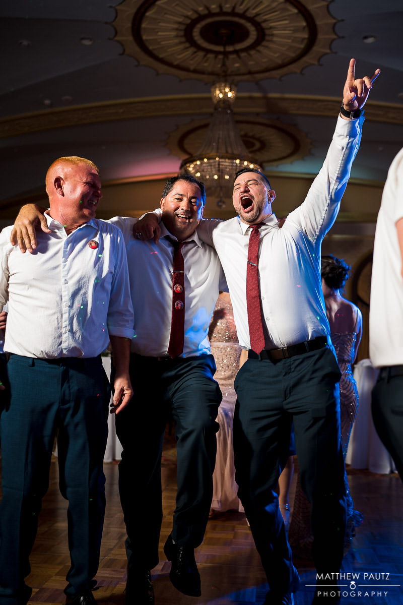 groomsmen dancing together at reception