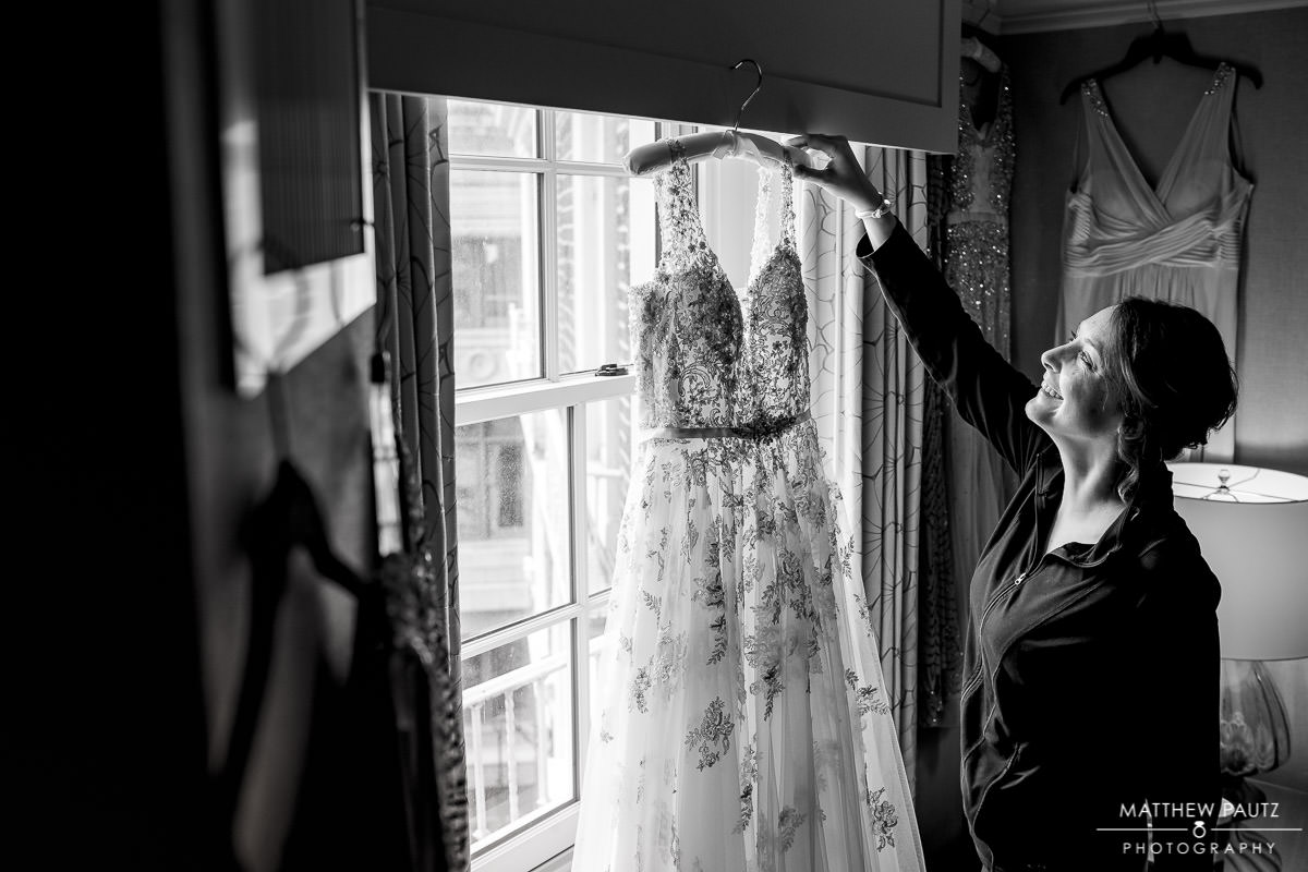 wedding dress hanging in the window of a hotel room