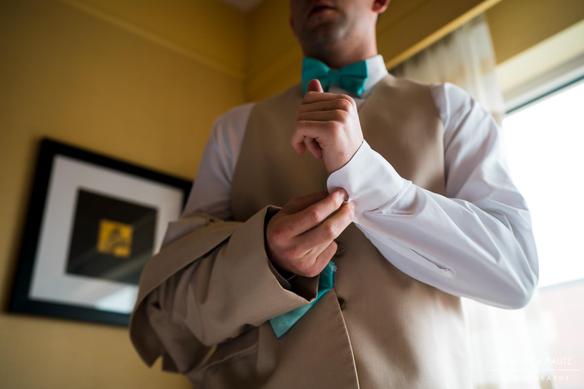 groom adjusting cufflinks before wedding