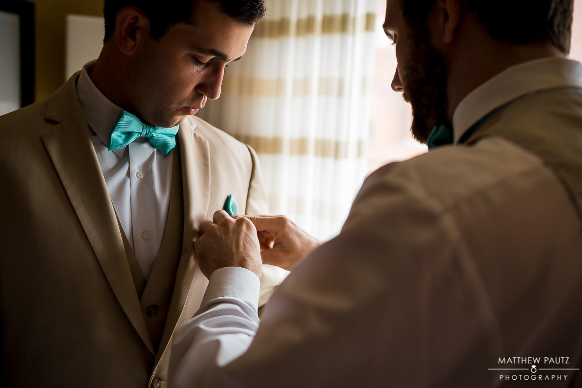 groom getting dressed for wedding ceremony