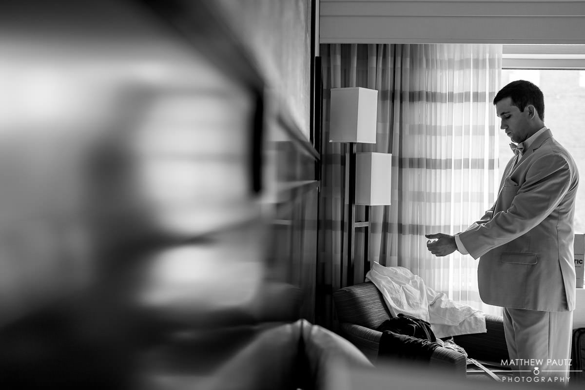 groom getting dressed in hotel room