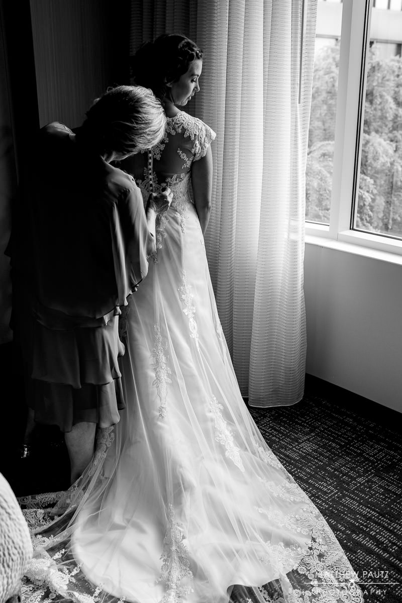 bride getting into her wedding dress before ceremony