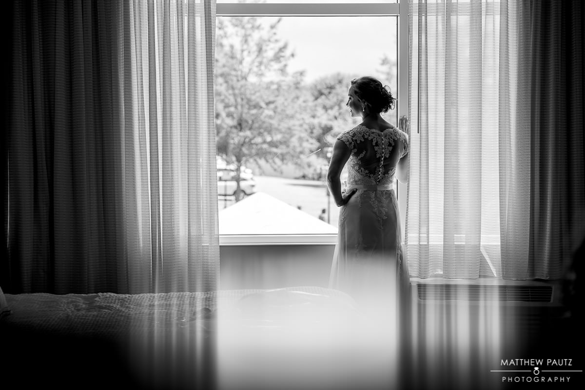 bride looking out window after getting dressed