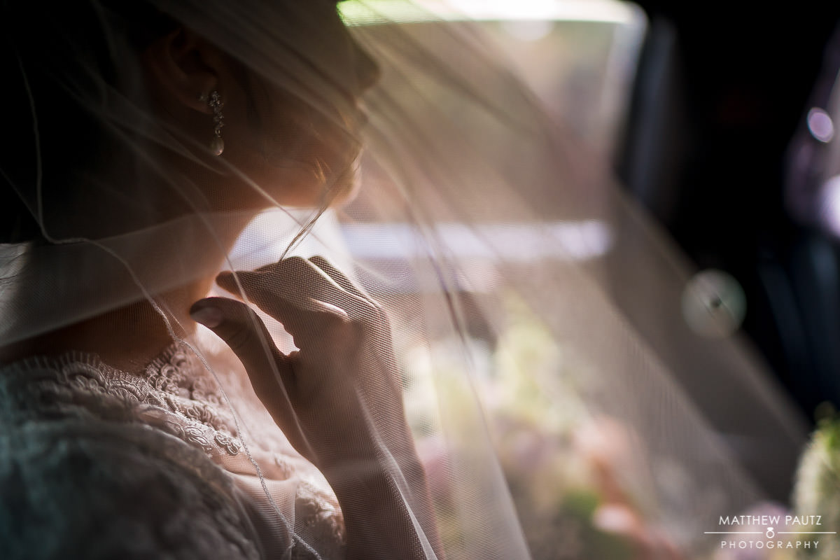 bride adjusting veil while riding in limo to wedding ceremony