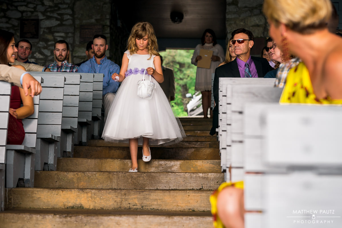 flower girl walking down the aisle at pretty place