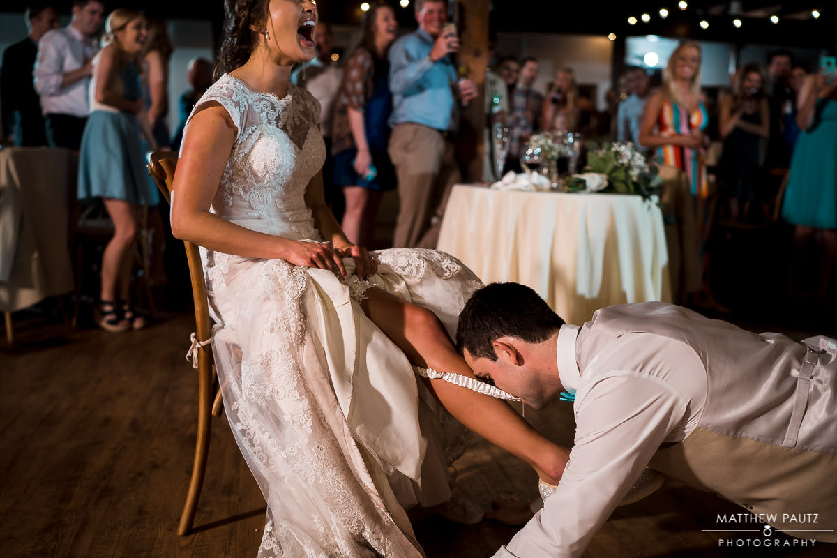 groom taking garter off bride at reception