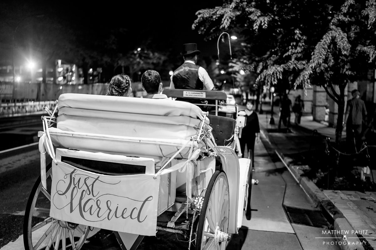 bride and groom leaving in horse-drawn carriage after wedding reception