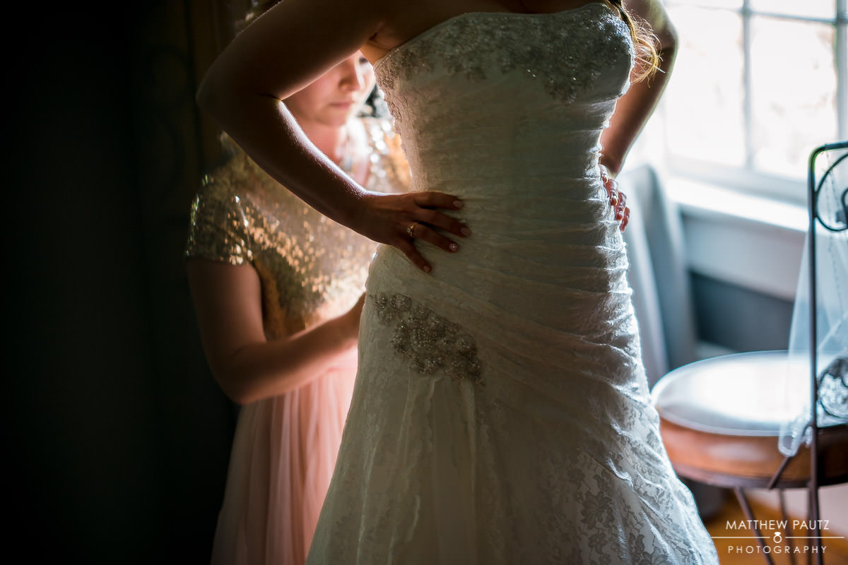 bridesmaid helping bride get into wedding dress