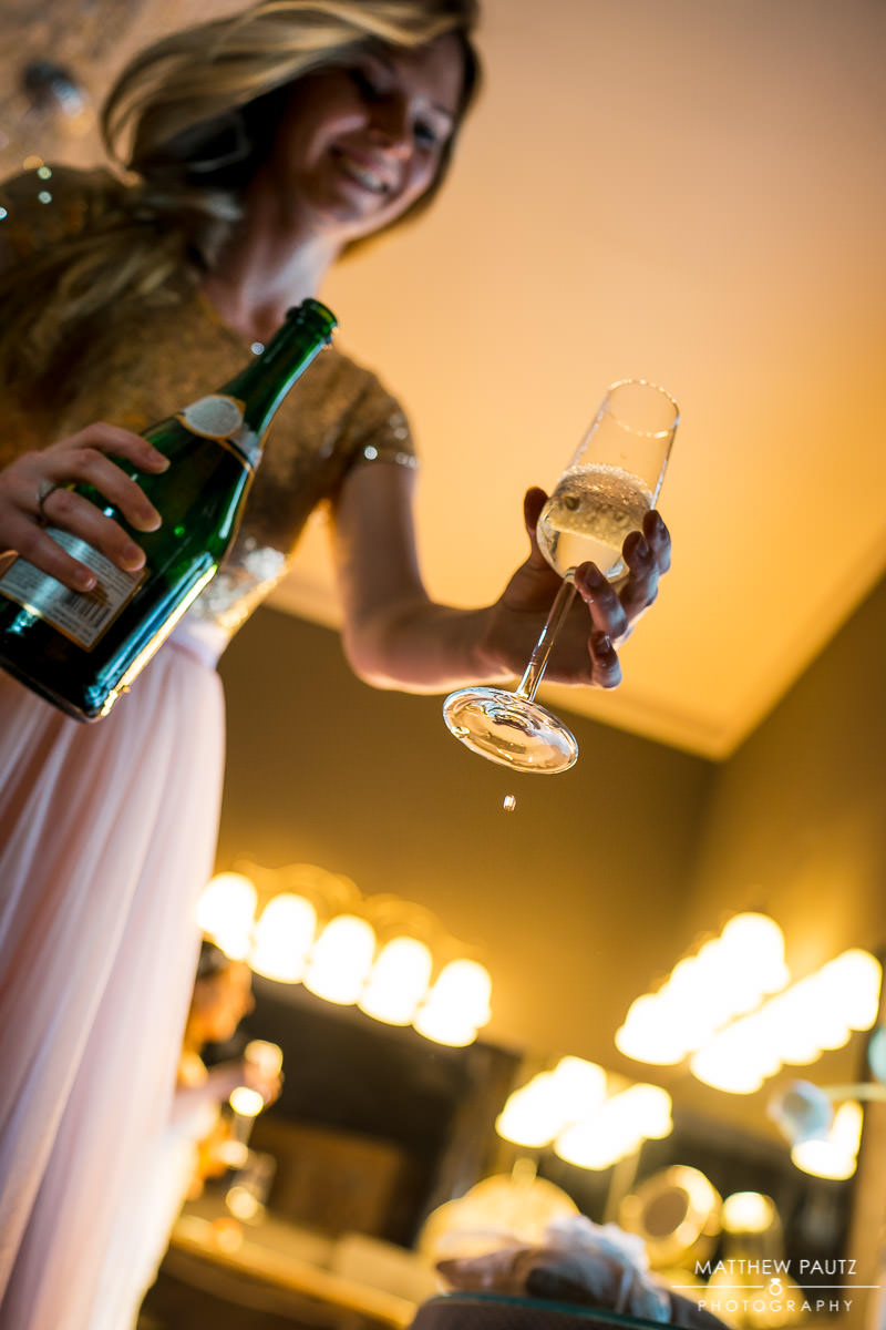 bridesmaid pouring champagne before wedding ceremony