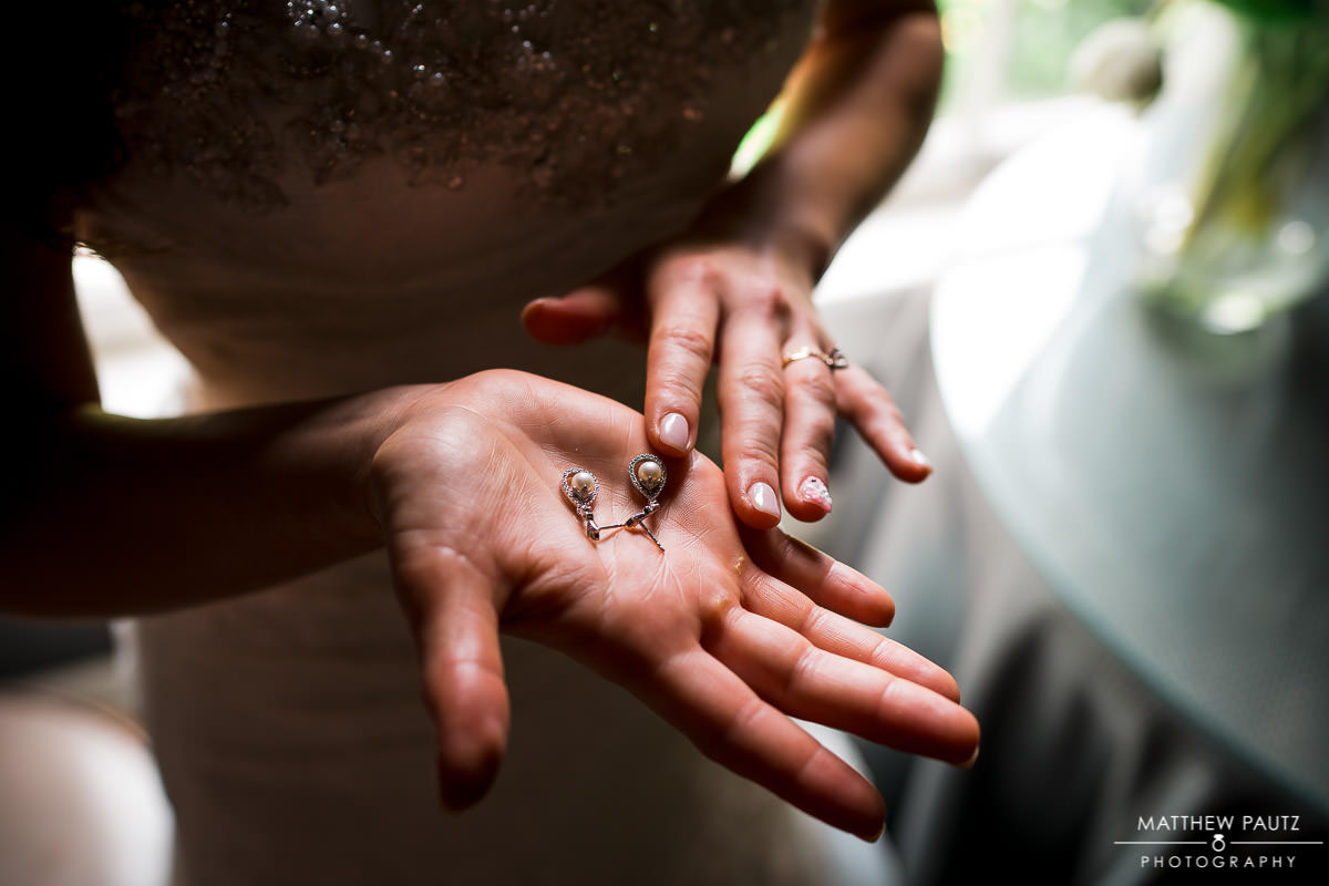 Bride holding earrings in her hand while getting dressed