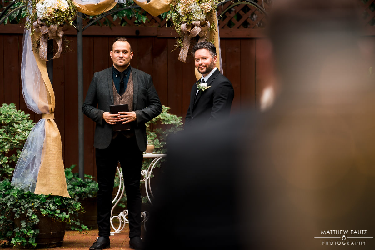 Groom watching bride walk down aisle at wedding ceremony